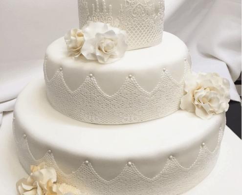 Svadobná torta s jedlou čipkou, ružami a perlami